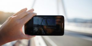 Tourist hand holding cell phone while taking a photograph of landscape in travel taking a picture